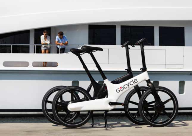 Pair of white GoCycles in front of large yacht